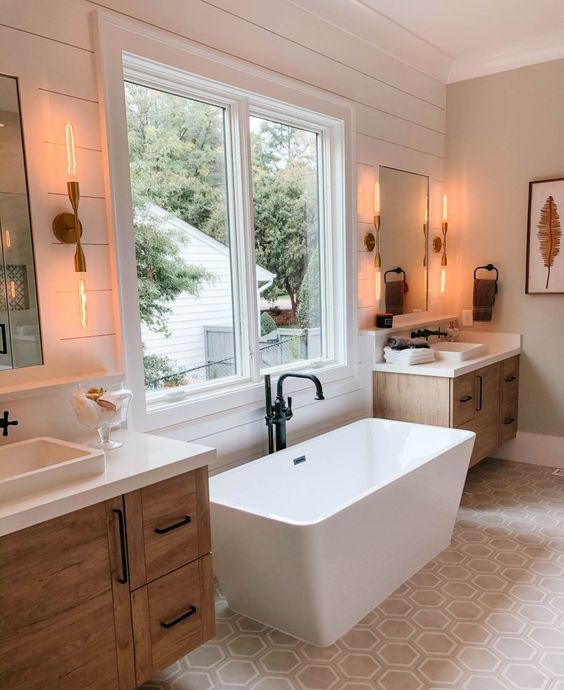 a modern country bathroom with white planked walls, a hexagon tile floor, wooden vanities, a modern tub and black fixtures