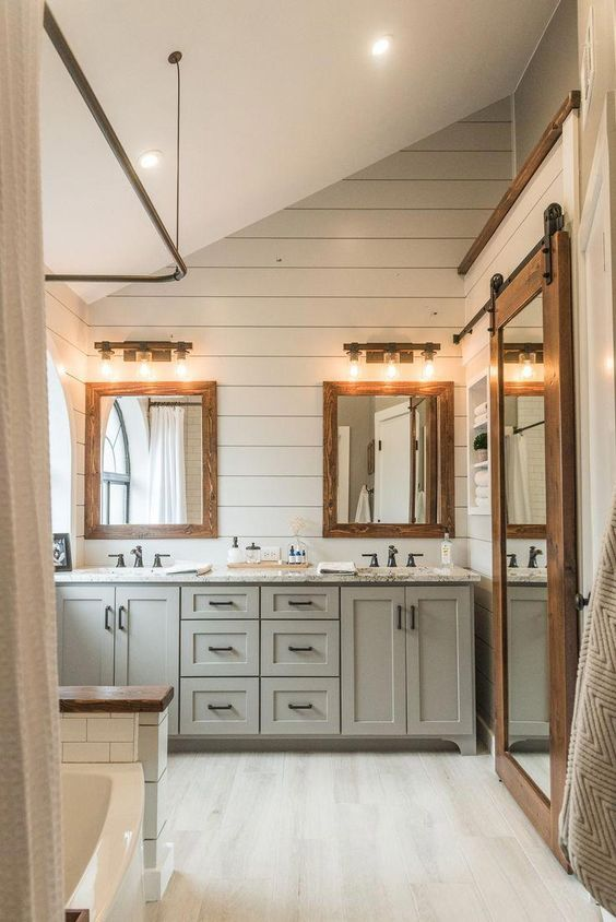 a modern country bathroom with white planked walls and a grey vanity, white subway tiles, mirrors in wooden frames with lights