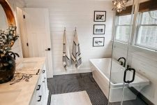 a modern country bathroom with white planked walls and a stained ceiling, a penny tile floor, white furniture and appliances and black fixtures