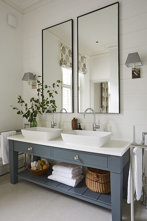 a modern country bathroom with white planked walls and a tiled floor, a double grey vanity, two tall mirrors and some greenery