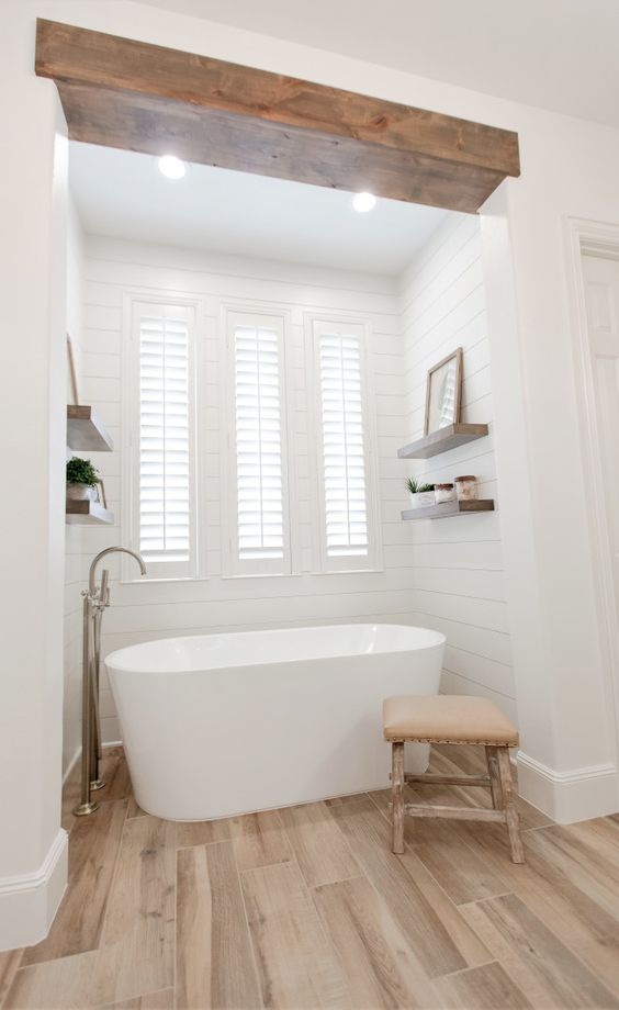 a modern country bathroom with white planked walls and laminate on the floor, a wooden beam, a bay window and a lovely bathtub