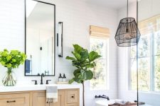 a modern country bathroom with white skinny tiles, a stained vanity, an oval tub, a pendant lamp and a skylight