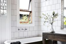 a modern country bathroom with white square and bright mosaic tiles, a black clawfoot tub, a dark stained vanity, pendant lamps and greenery