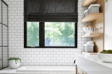 a modern country bathroom with white subway tiles and black herringbone ones, a bathtub clad with white marble, light stained furniture and a window with a shade