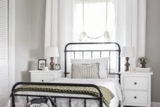 a modern country bedroom with a forged bed and white nightstands, baskets and a woven rug, neutral textiles and plants