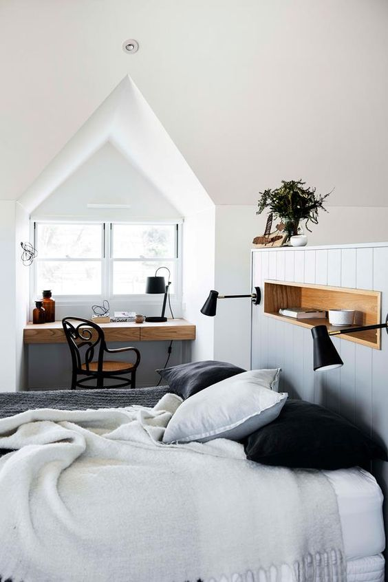 a modern country bedroom with a light blue half wall, a windowsill desk, a vintage chair and potted plants and neutral bedding