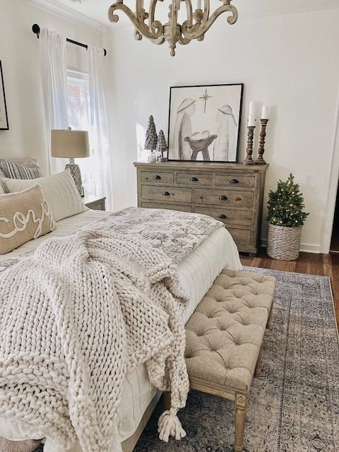 a modern country bedroom with a neutral bed and a tufted bench, a vintage wooden dresser, a wooden chandelier, wooden candle holders