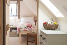 a modern country bedroom with a rough wooden frame on the window, simple wooden furniture, neutral and floral bedding