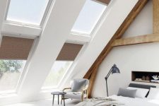 a modern country bedroom with an attic ceiling and lots of windows, wooden beams and a built-in fireplace, cool furniture and a sitting nook by the window