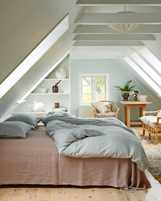 a modern country bedroom with an attic ceiling and wooden beams, skylights, open shelves, wooden furniture and a large bed is very welcoming