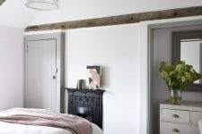 a modern country bedroom with dark stained wodoen beams, a non-workign fireplace, neutral furniture and neutral textiles