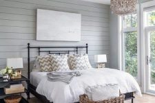 a modern country bedroom with grey planked walls, a black forged bed, neutral bedding, a wooden bead chandelier, a basket for storage