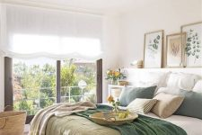 a modern country bedroom with natural touches, a ledge with artworks, a bed with green and white bedding and a large window