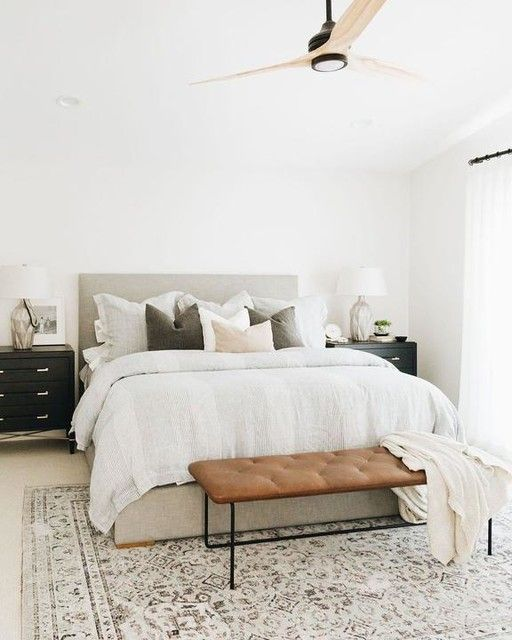 a modern country bedroom with neutral walls, a grey upholstered bed, a leather bench, black dresser nightstands and neutral textiles