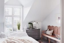 a modern country bedroom with stained beams on the ceiling, a carved wooden bench and a bed with neutral bedding, a potted plant and some decor