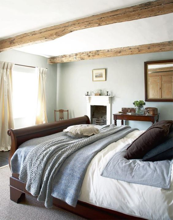 a modern country bedroom with wooden beams, a fireplace, a dark stained bed and a mirror plus some vintage furniture