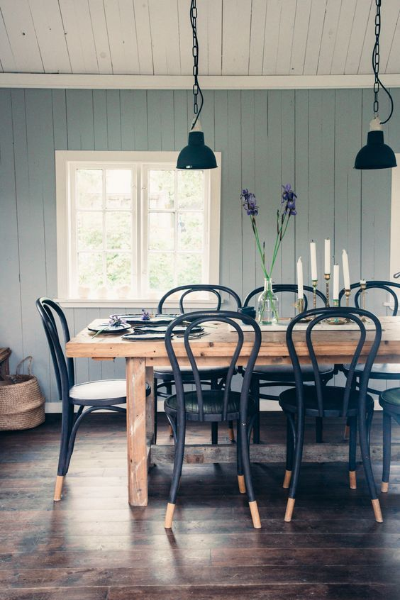 a modern country dining room with blue walls, a stained wooden table, black chairs, vintage black pendant lamps
