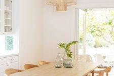 a modern country dining room with white buffets, a wooden trestle table and woven and rattan chairs plus a woven pendant lamp