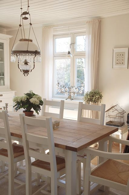 a modern country dining space with a simple wooden dining set, a large white buffet, a vintage chandelier and neutral textiles