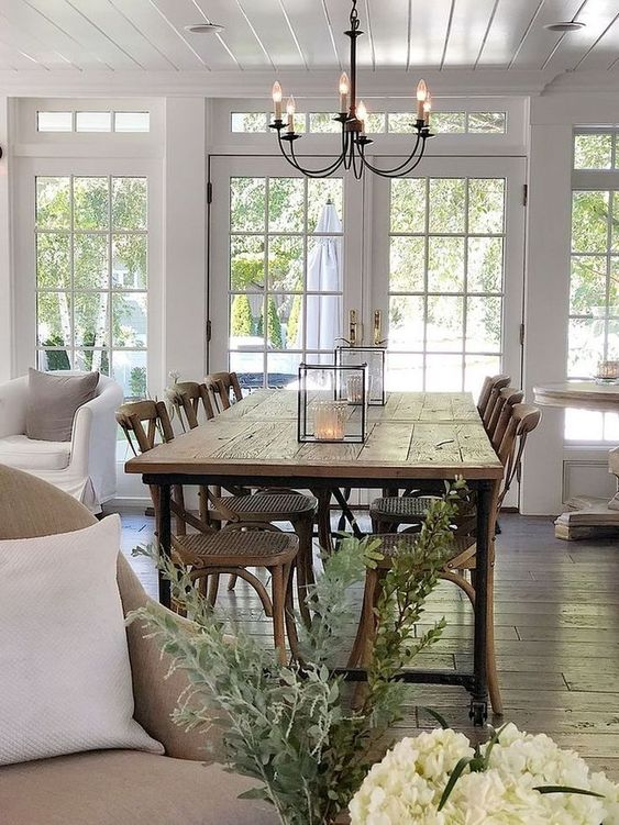 a modern country dining space with a stained table and chairs with woven seats, a vintage chandelier and cadle lanterns