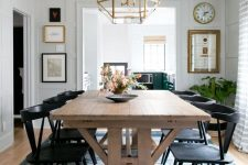 a modern country dining space with a stained trestle dining table, black chairs, a blue rug and a gilded faceted chandelier