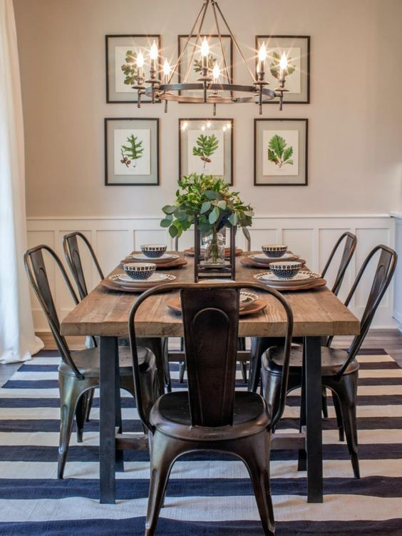 a modern country dining zone with a stained table, metal chairs, a striped rug, a large metal chandelier and an organic gallery wall