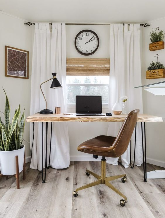 a modern country home office in creamy shades, with a hairpin desk, a leather chair, creamy curtains and potted plants on the floor and wall