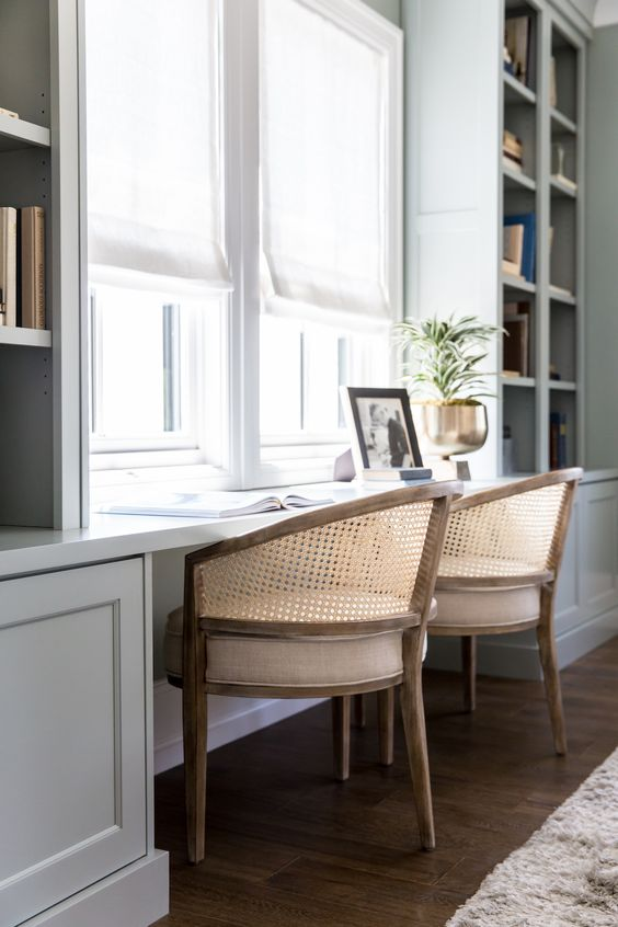 a modern country home office with a large built-in shelving unit that includes a double desk and rattan chairs