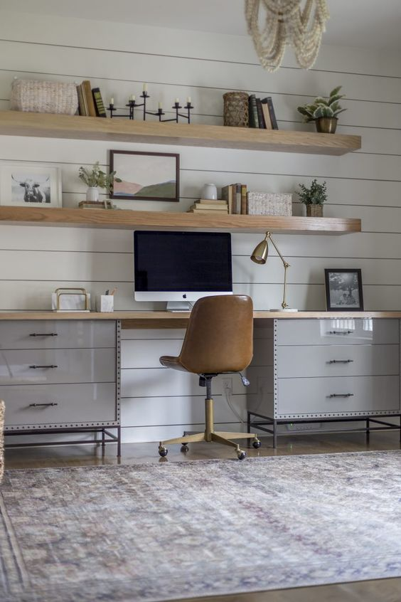 a modern country home office with a white planked wall, a grey desk, a leather chair, wooden slab floating shelves
