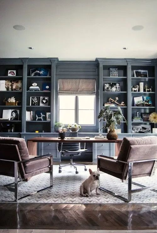 a modern country home office with built-in grey storage units, a large desk and leather chairs plus printed shades