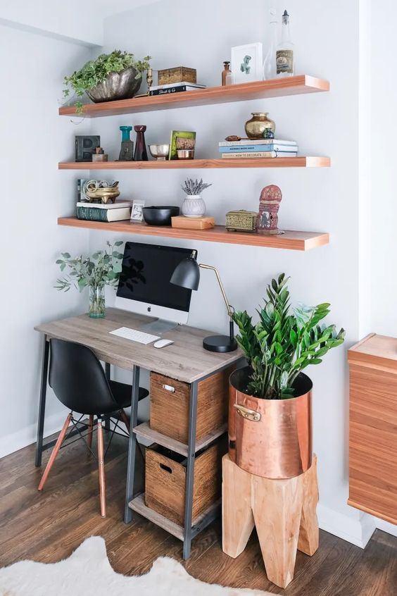 a modern country home office with floating shelves, an industrial desk with crate storage, a stool and a copper planter plus some greenery