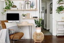 a modern country home office with floating shelves and a hairpin desk, a leather chair, a wooden stool and potted plants