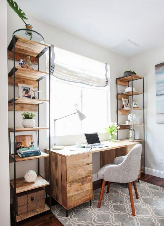 a modern country home office with open shelving units and a rough wooden desk, a grey chair, potted plants and a striped shade