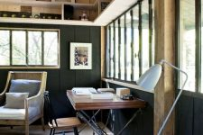 a modern country home office with wooden beams, black planked walls, a cool desk and a vintage chair, a rattan chair and a floor lamp
