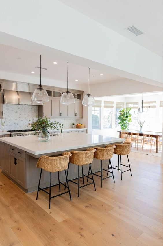 a modern country kitchen in dove grey, with shaker style cabinets, a large kitchen island, pendant lamp, woven stools
