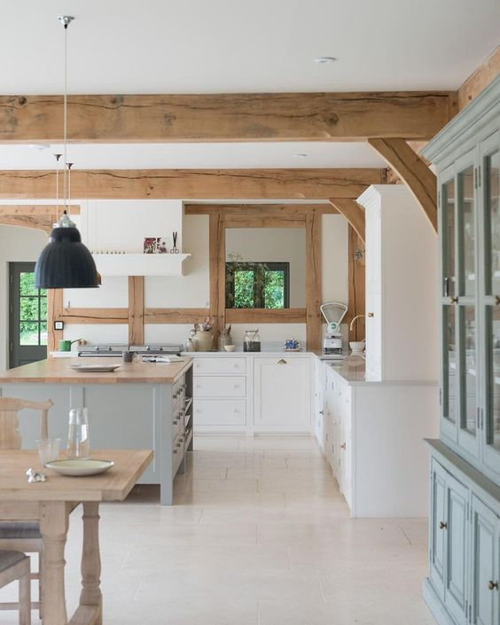 a modern country kitchen in white, light blue and light grey, butcherblock countertops, wooden beams on the ceiling and pendant lamps