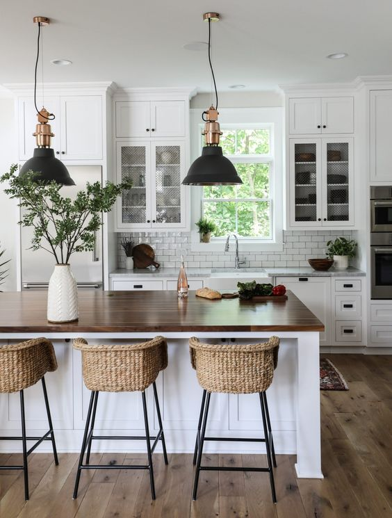 a modern country kitchen in white, with cool cabinets, a large kitchen island with a butcherblock countertop, pendant lamps and woven stools