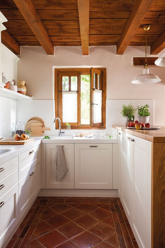 a modern country kitchen with a tiled floor, white cabinets and a raised butcherblock countertops, a wooden ceiling with beams and frames on the window