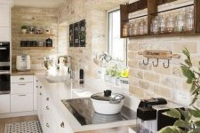 a modern country kitchen with exposed brick, white cabinets, white and butcherblock countertops and laminate flooring
