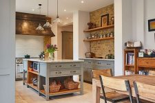 a modern country kitchen with exposed brick, white subway tiles, light grey cabinets and a kitchen island, pendant lamps and metallic fixtures