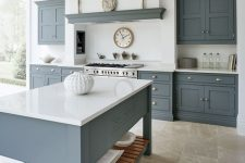 a modern country kitchen with graphite grey cabinets and a kitchen island, white countertops and a built-in hood plus a glazed wall