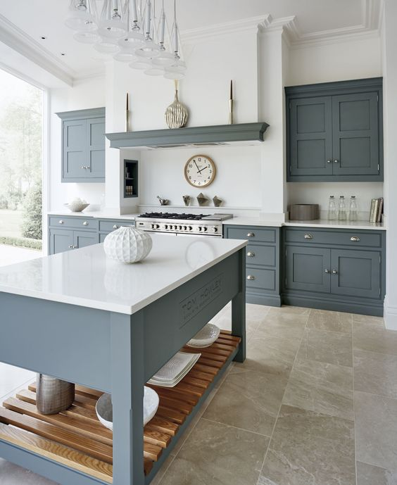 a modern country kitchen with graphite grey cabinets and a kitchen island, white countertops and a built in hood plus a glazed wall