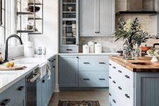 a modern country kitchen with light grey cabinets, butcherblock, white countertops, black fixtures and a vintage metal lamp