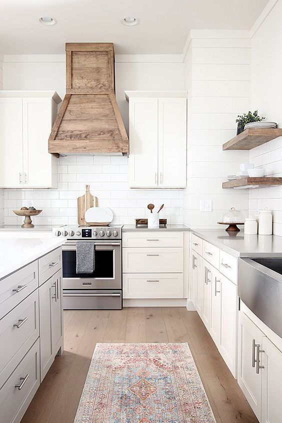 a modern country kitchen with shaker style cabinets, a white subway tile backsplash, a wooden hood and floating shelves