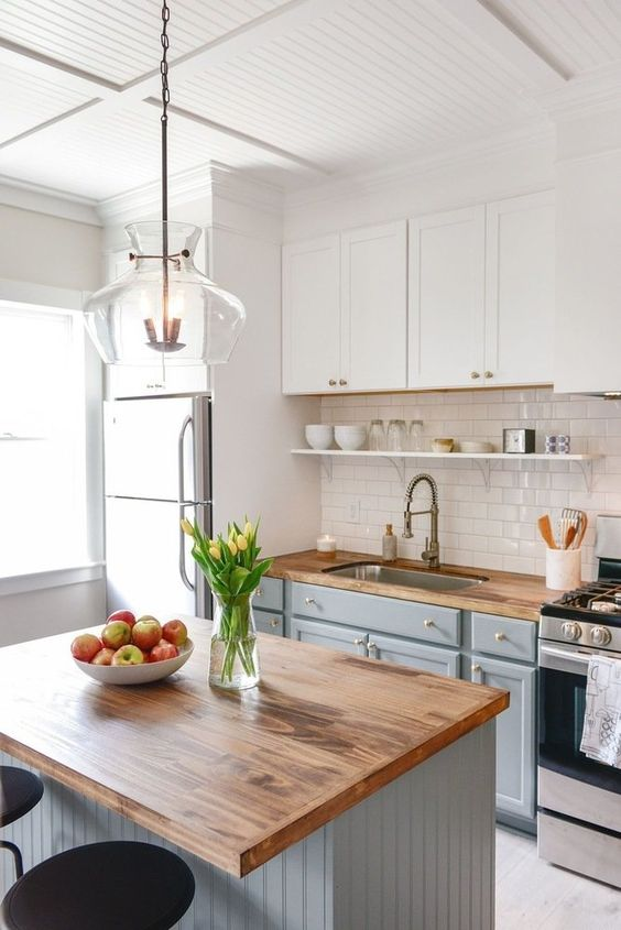 a modern country kitchen with white and light grey cabinets, butcherblock countertops, a shiny subway tile backsplash and a pendant lamp