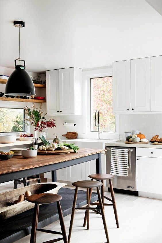a modern country kitchen with white cabinetry and a black kitchen island plus a butcherblock countertop and black pendant lamps