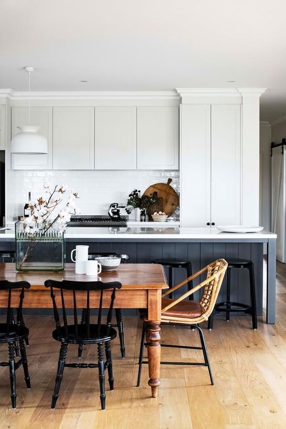 a modern country kitchen with white cabinets and a navy kitchen island, a vintage table and chairs for the dining space