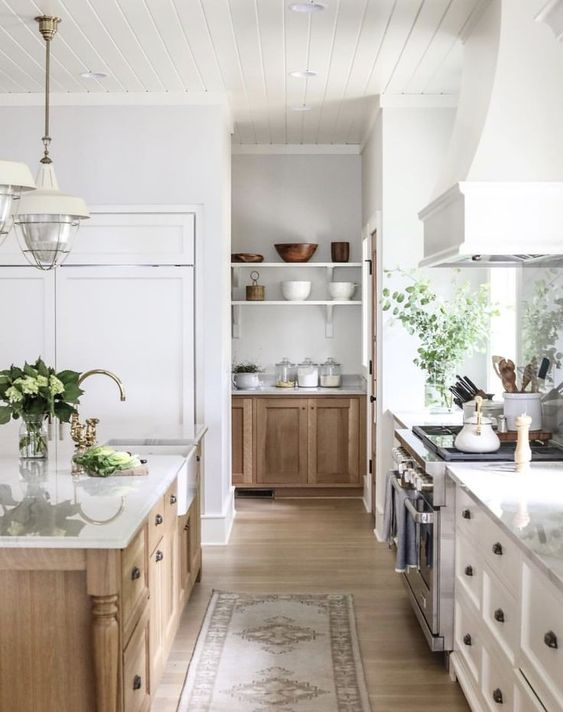 a modern country kitchen with white shaker style cabinets, a light stained kitchen island, white countertops and a large hood plus pendant lamps