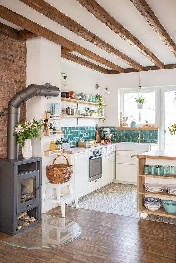a modern country kitchen with white walls and white cabinetry, wooden beams on the ceiling, a hearth and a basket plus wooden shelves