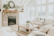 a modern country living room designed in neutrals, with a fireplace clad with stone, cozy furniture and printed textiles
